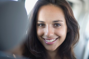 Young woman with dark hair in car smiling